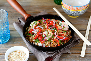Buckwheat noodles with shrimp, peppers and tomatoes in a frying
