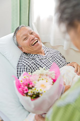 笑顔のシニア男性患者とお見舞いの女性