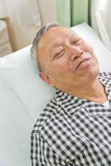 ベッドに寝ているシニア男性患者