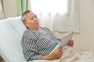 ベッドでタブレットを見るシニア男性患者