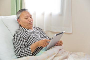 ベッドでタブレットを使うシニア男性患者