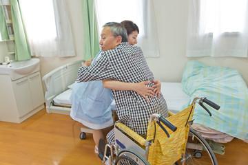 シニア男性患者を車いすへ乗せる看護師