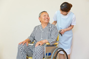 シニア男性患者の車いすを押す看護師