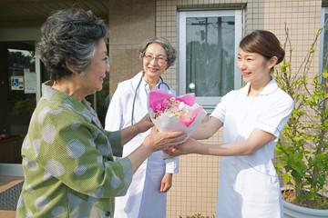 退院するシニア女性と女医と看護師