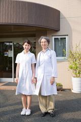 病院の前に並んで立つ女医と看護師