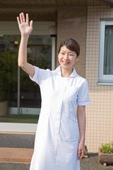 病院の前で手を振る看護師
