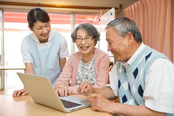 パソコンを使うシニアと教える介護福祉士