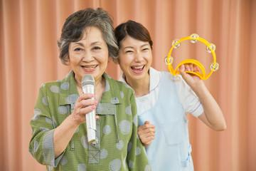 カラオケを楽しむシニア女性と介護福祉士
