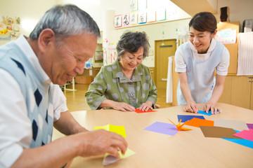折り紙を折るシニアと介護福祉士