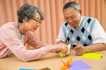 折り紙を折るシニア男性とシニア女性