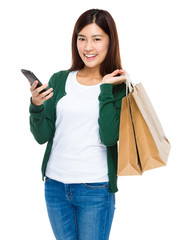 Woman with shopping bag and holding mobile phone