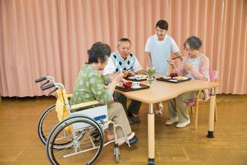 老人ホームで食事するシニアと介護福祉士