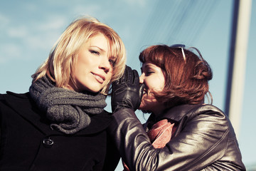 Two happy young fashion women teeling secrets outdoor