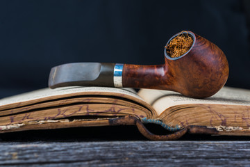 smoking pipe on the opened old book in wooden grey table.