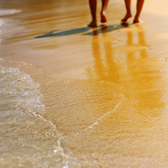 Male and female feet walk on the sandy beach