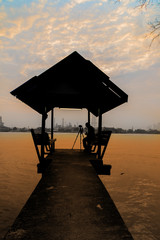 Silhouette waterfront pavilion with photographer