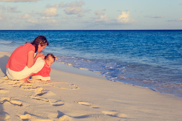 mother and little daughter drawing heart on beach