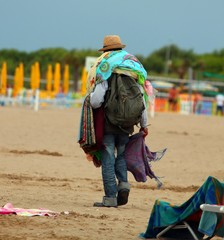 abusive Peddler with fabrics and dresses walking on the beach gl