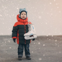 cute little boy  holds the skates wearing warm winter clothes  g
