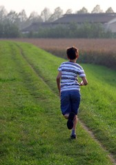 young child runs along a country road at sunset