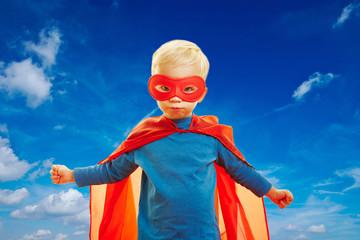Junge fliegt als Superheld vor Himmel