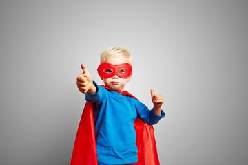Kind als Superheld hält Daumen hoch