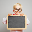 Kind mit Brille hält leere Tafel