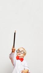 Kind als Zauberer hält Zauberstab in die Luft