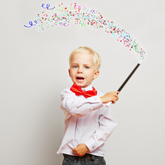 Kind zaubert Konfetti aus Zauberstab