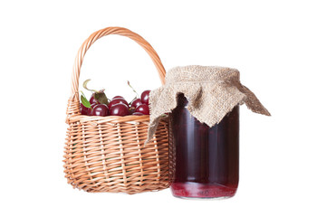 Bank with cherry jam and a basket with ripe cherries