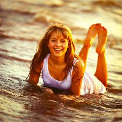 Beautiful young girl enjoys the sun and the ocean.