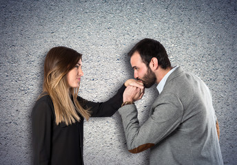 man kissing a woman's hand over textured background