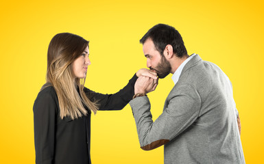 man kissing a woman's hand over yellow background.