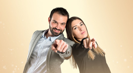 Couple pointing to the front over gloss background