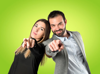 Couple pointing to the front over green background
