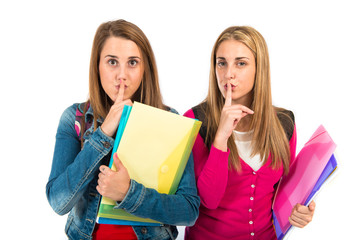Students making silence gesture over white background