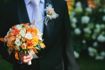 Groom is holding bridal bouquet