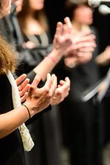 Mani di coriste che battono il tempo musicale, fuoco selettivo