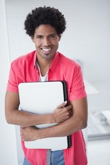 Smiling casual businessman holding laptop