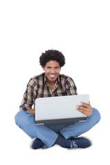 Smiling man sitting and using laptop