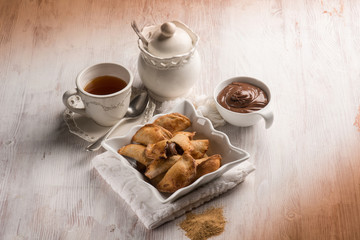 tea cup and cookie stuffed with chocolate cream