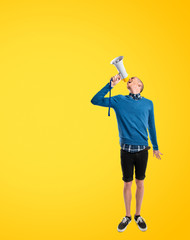 Redhead man shouting by megaphone over yellow background