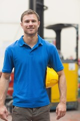 Handsome warehouse worker smiling at camera