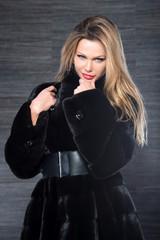 Fashion beautiful blonde woman posing in fur coat. Winter Girl