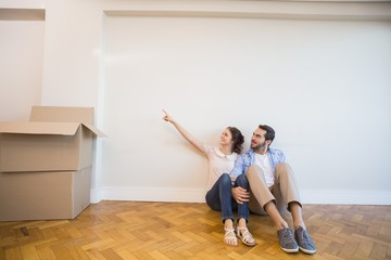 Cute couple pointing to the wall