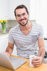 Young man using laptop while having coffee