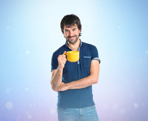 Man holding a cup of coffee over blue background