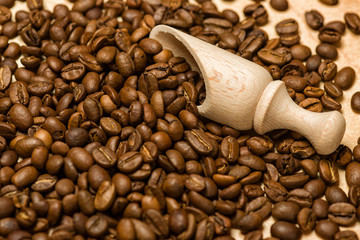 coffee seeds with wooden shovel on wood background