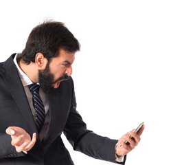 Furious businessman talking to mobile over white background