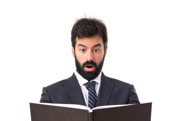 Surprised businessman reading a book over white background